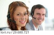 Купить «Call centre agents wearing headsets», видеоролик № 29680721, снято 22 ноября 2011 г. (c) Wavebreak Media / Фотобанк Лори