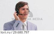 Купить «Handsome businessman talking on a headset», видеоролик № 29680797, снято 22 ноября 2011 г. (c) Wavebreak Media / Фотобанк Лори
