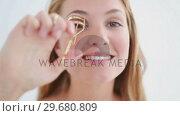 Купить «Happy blonde woman using a curler», видеоролик № 29680809, снято 22 ноября 2011 г. (c) Wavebreak Media / Фотобанк Лори