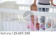 Купить «Woman putting her baby girl in a cradle », видеоролик № 29681545, снято 25 ноября 2011 г. (c) Wavebreak Media / Фотобанк Лори