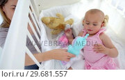 Купить «Woman playing dolls with her baby», видеоролик № 29681557, снято 25 ноября 2011 г. (c) Wavebreak Media / Фотобанк Лори