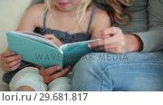 Купить «Mother helping her daughter read a book», видеоролик № 29681817, снято 25 ноября 2011 г. (c) Wavebreak Media / Фотобанк Лори