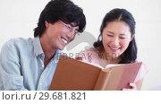 Купить «Man and a woman reading a book together», видеоролик № 29681821, снято 25 ноября 2011 г. (c) Wavebreak Media / Фотобанк Лори