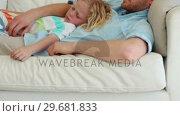 Купить «Father holds his son as they sleep together», видеоролик № 29681833, снято 25 ноября 2011 г. (c) Wavebreak Media / Фотобанк Лори