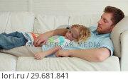 Купить «Son lies with his father as they sleep», видеоролик № 29681841, снято 25 ноября 2011 г. (c) Wavebreak Media / Фотобанк Лори