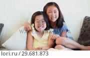 Купить «Girl hugging her sister as they sit together», видеоролик № 29681873, снято 25 ноября 2011 г. (c) Wavebreak Media / Фотобанк Лори