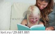 Купить «Girl laughing as she reads a book with her mother», видеоролик № 29681881, снято 25 ноября 2011 г. (c) Wavebreak Media / Фотобанк Лори