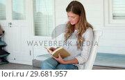 Купить «Woman happily reading a book», видеоролик № 29681957, снято 25 ноября 2011 г. (c) Wavebreak Media / Фотобанк Лори