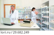 Pharmacist talking on the phone in a pharmacy with an other pharmacist. Стоковое видео, агентство Wavebreak Media / Фотобанк Лори