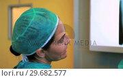 Купить «Two surgeons examining a Xray», видеоролик № 29682577, снято 24 апреля 2012 г. (c) Wavebreak Media / Фотобанк Лори