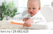 Купить «Baby sitting and plays with orange spoon», видеоролик № 29682625, снято 18 мая 2012 г. (c) Wavebreak Media / Фотобанк Лори