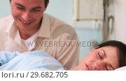 Купить «Happy father looking at his wife and a newborn baby sleeping», видеоролик № 29682705, снято 27 апреля 2012 г. (c) Wavebreak Media / Фотобанк Лори
