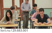 Students in exam hall . Стоковое видео, агентство Wavebreak Media / Фотобанк Лори