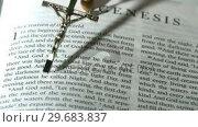 Купить «Rosary beads falling onto the book of genesis», видеоролик № 29683837, снято 18 января 2013 г. (c) Wavebreak Media / Фотобанк Лори