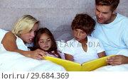 Parents reading a fairytale to their children. Стоковое видео, агентство Wavebreak Media / Фотобанк Лори