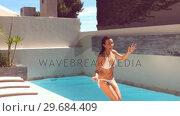 Купить «Pretty woman leaping in swimming pool», видеоролик № 29684409, снято 25 марта 2013 г. (c) Wavebreak Media / Фотобанк Лори