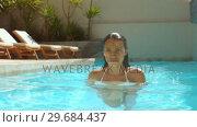 Купить «Beautiful woman walking in swimming pool», видеоролик № 29684437, снято 25 марта 2013 г. (c) Wavebreak Media / Фотобанк Лори