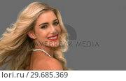 Купить «Attractive woman tossing her hair on grey screen», видеоролик № 29685369, снято 8 апреля 2013 г. (c) Wavebreak Media / Фотобанк Лори