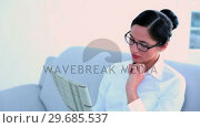 Купить «Attractive businesswoman sitting on couch and reading newspaper», видеоролик № 29685537, снято 10 июля 2013 г. (c) Wavebreak Media / Фотобанк Лори