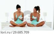 Купить «Content young women eating cereal sitting on bed», видеоролик № 29685709, снято 14 августа 2013 г. (c) Wavebreak Media / Фотобанк Лори