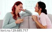 Купить «Content young women drinking wine while sitting chatting on couch», видеоролик № 29685717, снято 15 августа 2013 г. (c) Wavebreak Media / Фотобанк Лори