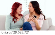 Lovely happy women phoning excited with smartphone sitting on couch. Стоковое видео, агентство Wavebreak Media / Фотобанк Лори