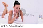 Купить «Young attractive woman lying on her bed using her laptop», видеоролик № 29685753, снято 18 июля 2013 г. (c) Wavebreak Media / Фотобанк Лори