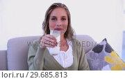 Купить «Gleeful woman drinking a glass of milk and showing it», видеоролик № 29685813, снято 31 мая 2013 г. (c) Wavebreak Media / Фотобанк Лори