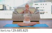 Купить «Content calm woman meditating in her living room», видеоролик № 29685825, снято 31 июля 2013 г. (c) Wavebreak Media / Фотобанк Лори