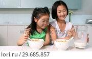 Купить «Two girls eating cereal», видеоролик № 29685857, снято 29 августа 2013 г. (c) Wavebreak Media / Фотобанк Лори