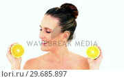 Купить «Pretty woman showing two orange halves», видеоролик № 29685897, снято 5 июня 2013 г. (c) Wavebreak Media / Фотобанк Лори