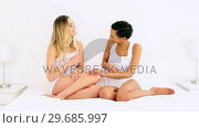 Купить «Two pretty friends laughing and hugging each other on bed», видеоролик № 29685997, снято 13 августа 2013 г. (c) Wavebreak Media / Фотобанк Лори
