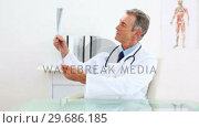 Купить «Mature doctor examining at xray at his desk», видеоролик № 29686185, снято 4 октября 2013 г. (c) Wavebreak Media / Фотобанк Лори