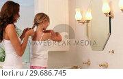 Mother plaiting her little girls hair in the morning. Стоковое видео, агентство Wavebreak Media / Фотобанк Лори