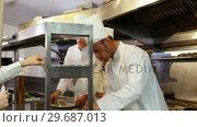 Купить «Chefs preparing plates», видеоролик № 29687013, снято 23 ноября 2015 г. (c) Wavebreak Media / Фотобанк Лори