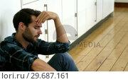Купить «Man is sitting against a wall with a sad expression on his face», видеоролик № 29687161, снято 16 декабря 2015 г. (c) Wavebreak Media / Фотобанк Лори