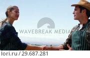 Купить «Smiling couple shaking hand while interacting in field», видеоролик № 29687281, снято 16 февраля 2016 г. (c) Wavebreak Media / Фотобанк Лори