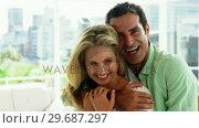 Купить «Portrait of young couple embracing each other in living room», видеоролик № 29687297, снято 3 февраля 2016 г. (c) Wavebreak Media / Фотобанк Лори