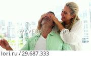 Купить «Smiling woman covering mans eyes in living room at home», видеоролик № 29687333, снято 3 февраля 2016 г. (c) Wavebreak Media / Фотобанк Лори