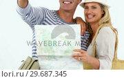 Купить «Smiling couple looking at map and pointing against white background», видеоролик № 29687345, снято 3 февраля 2016 г. (c) Wavebreak Media / Фотобанк Лори
