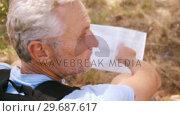 Купить «Hiker looking at map », видеоролик № 29687617, снято 9 февраля 2016 г. (c) Wavebreak Media / Фотобанк Лори