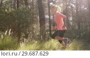 Woman jogging through forest. Стоковое видео, агентство Wavebreak Media / Фотобанк Лори