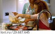 Купить «Mother and daughter are cooking cupcakes together », видеоролик № 29687645, снято 19 февраля 2016 г. (c) Wavebreak Media / Фотобанк Лори