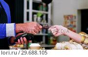 Купить «Customer making payment through payment terminal machine at counter», видеоролик № 29688105, снято 30 мая 2016 г. (c) Wavebreak Media / Фотобанк Лори
