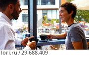 Купить «Businesspeople interacting while having coffee», видеоролик № 29688409, снято 20 июля 2016 г. (c) Wavebreak Media / Фотобанк Лори