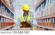 Купить «Warehouse worker writing on clipboard», видеоролик № 29688581, снято 23 марта 2016 г. (c) Wavebreak Media / Фотобанк Лори