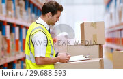 Купить «Warehouse worker writing on clipboard», видеоролик № 29688593, снято 23 марта 2016 г. (c) Wavebreak Media / Фотобанк Лори