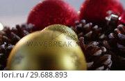 Купить «Close-up of christmas bauble and pine cone», видеоролик № 29688893, снято 30 августа 2016 г. (c) Wavebreak Media / Фотобанк Лори