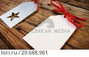 Купить «Close-up christmas tag kept in row on wooden plank», видеоролик № 29688961, снято 30 августа 2016 г. (c) Wavebreak Media / Фотобанк Лори