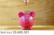 Купить «Hand dropping coin into piggy bank», видеоролик № 29689301, снято 8 июня 2016 г. (c) Wavebreak Media / Фотобанк Лори